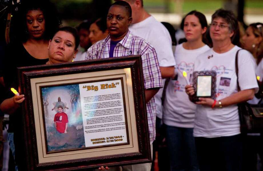 Maria Velasquez, front, holds a picture of her son Enrique Rick Velasquez, who was murdered in 2009, during the National Day of Remembrance for Murder Victims outside Houston City Hall. The third annual event is sponsored by the local chapter of Parents of Murdered Children and the U.S. Department of Justice.  Photo: Nick De La Torre, Houston Chronicle / © 2011 Houston Chronicle