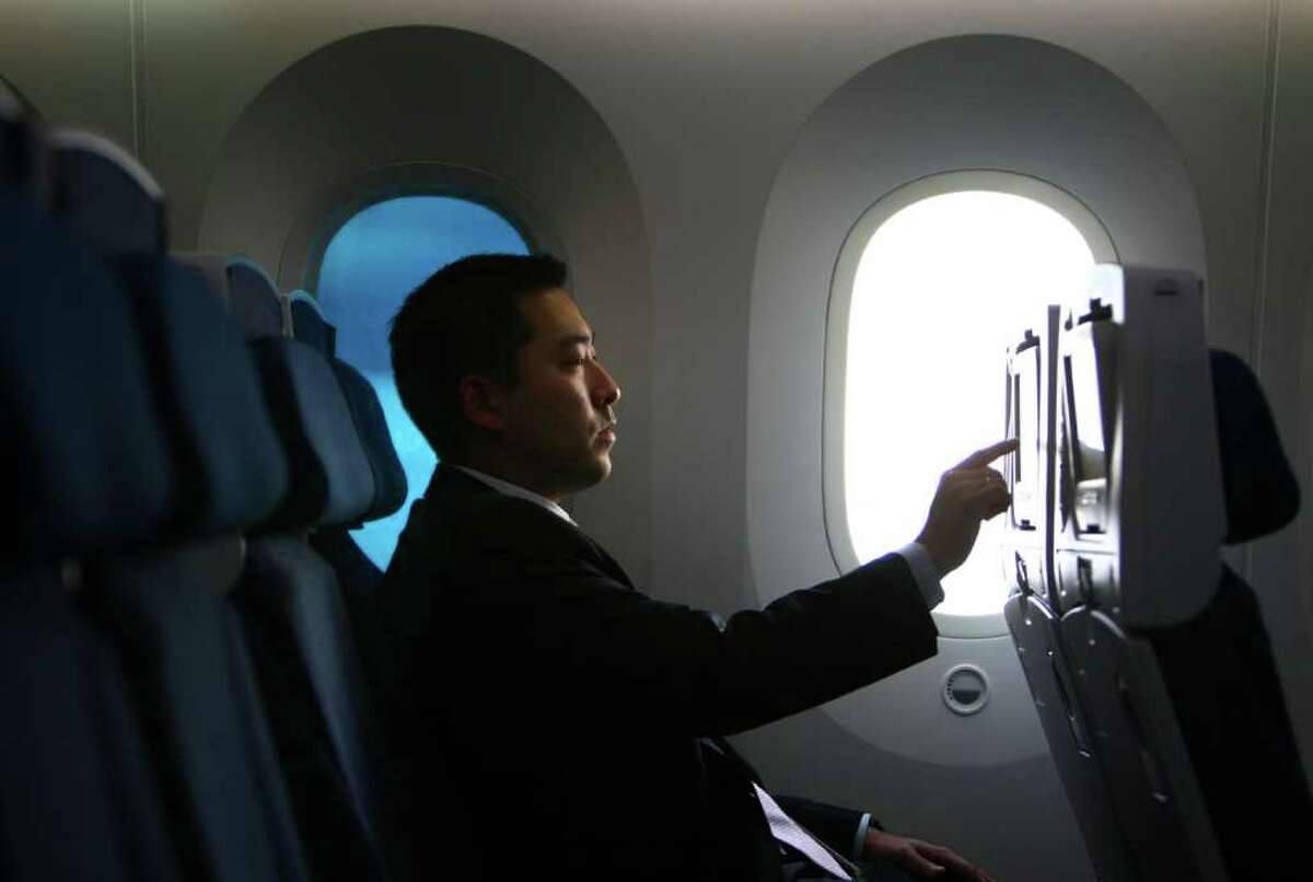 Kevin Yoo, a Boeing communications specialist, tries a touch screen aboard the second 787 destined for launch customer All Nippon Airways during a 787 tour at the Boeing assembly plant in Everett on Sunday, September 25, 2011. Boeing is set to deliver the first 787 to launch customer ANA.