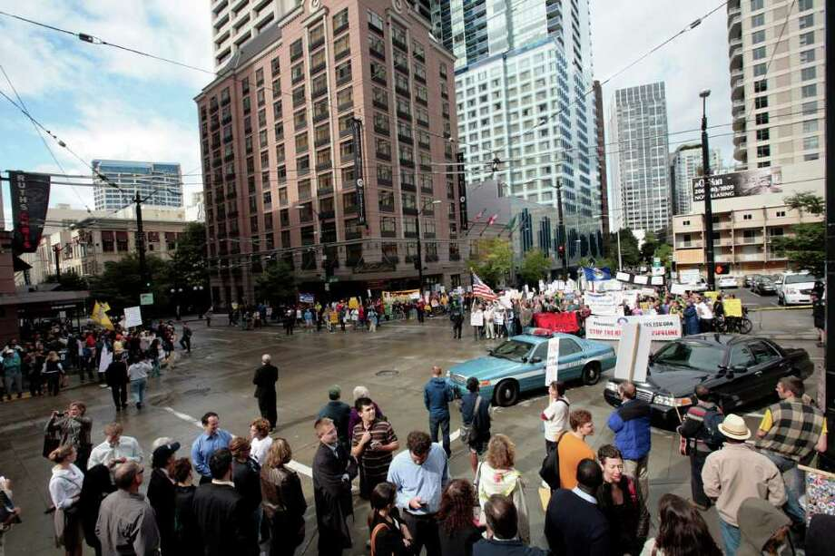 About 100 people rally as guests arrive for a fundraising event held by President Barack Obama in downtown Seattle, Sunday, Sept. 25, 2011. Streets including the corner of Pine Street and 8th Avenue were blocked off around the Paramount Theatre. Photo: Meryl Schenker / ASSOCIATED PRESS