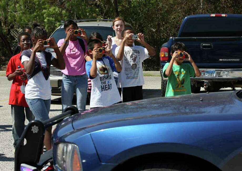 "Children from SAMMinistries photograph a police car in Castle Hills as part of the ""Pictures of Hope"" program for youngsters in shelters. Photo: Jerry Lara/glara@express-news.net / SAN ANTONIO EXPRESS-NEWS"