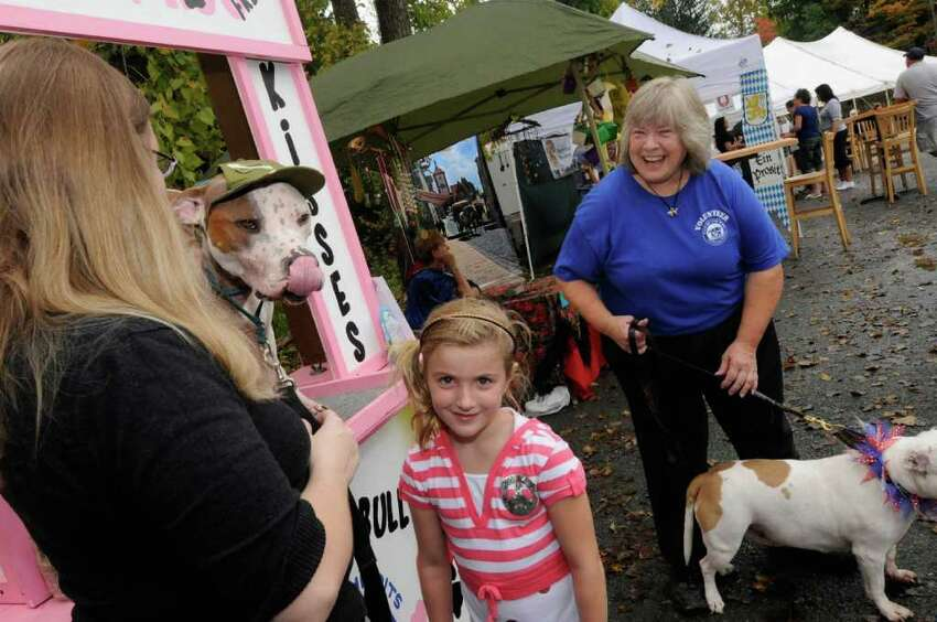 Seven-year-old Gabi Mohos smiles after getting a lick from Trooper, a pit bull belonging to Heather Babcock, left, as he works a kissing booth to raise funds for Out of the Pits' Fix-A-Bull spay/neuter program at the Uncle Marty's Oktoberfest in Averill Park, N.Y., Saturday, Sept. 24, 2011. Babcock is looking for a foster home for Trooper while she is deployed in Afghanistan. ( Michael P. Farrell/Times Union)