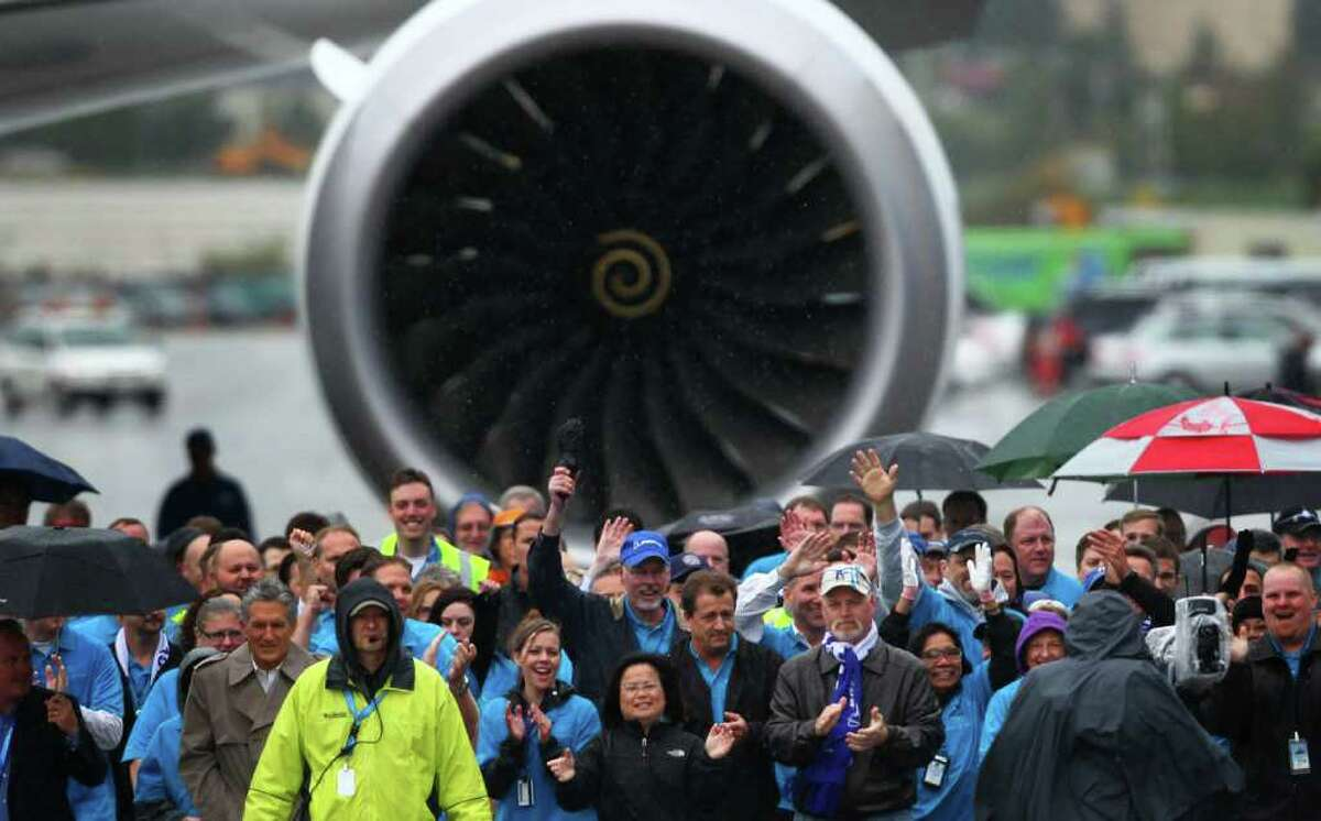 Boeing workers lead a 787 toward a ceremony marking delivery of the first Boeing 787 to launch customer All Nippon Airways on Monday at the Boeing plant in Everett.