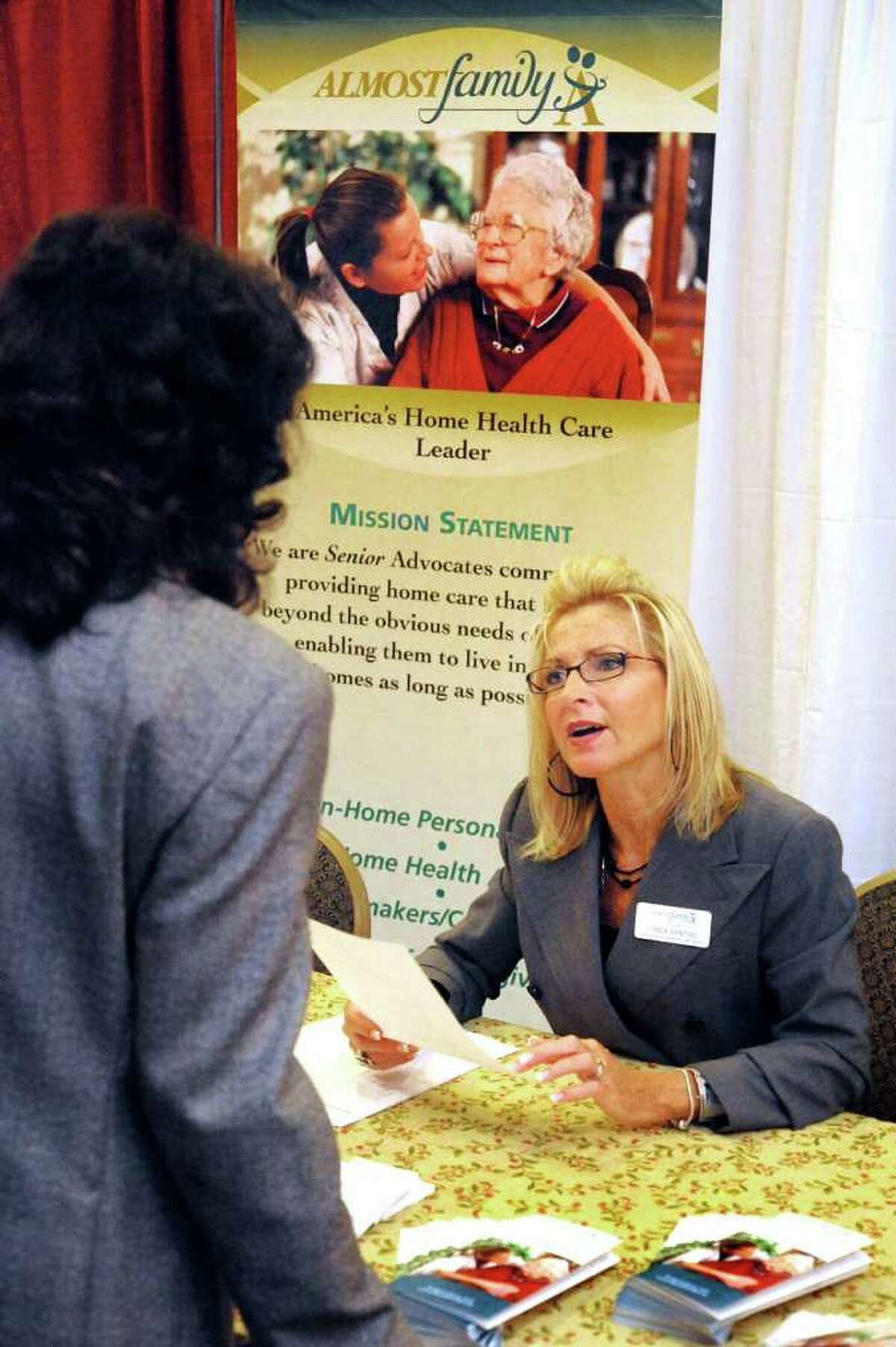 Linda Santini, of Almost Family, talks to a job-seeker during Career Fair 2011 at the Ethan Allen Inn in Danbury Monday, Sept. 26, 2011.