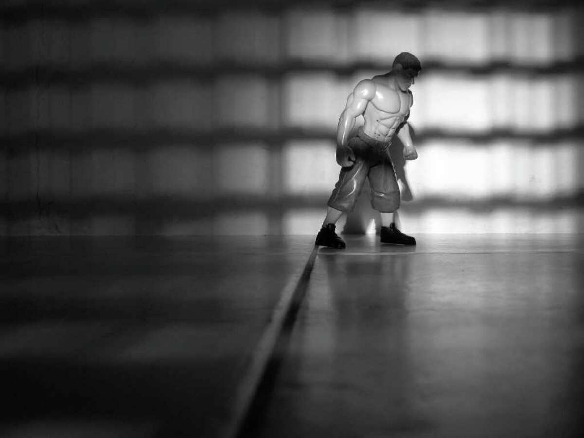 In this photo taken May 22, 2011 and released by blind photographer Alberto Loranca, a toy wrestler stands in the shadows of a fence.