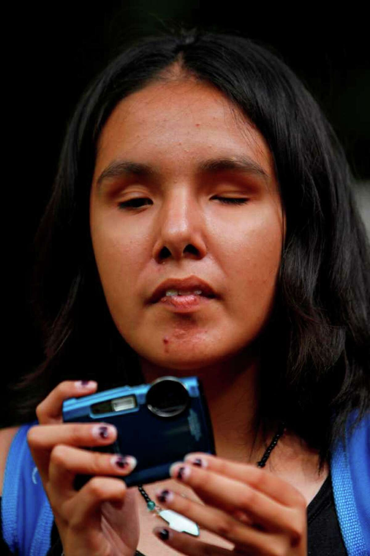 In this photo taken Sept. 7, 2011, Nancy Sarahi feels her camera as she prepares to take a photograph at a park in Mexico City.