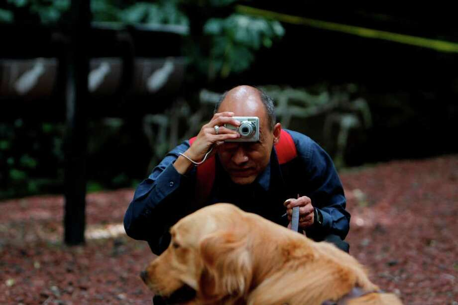 In this photo taken Sept. 7, 2011, Jose Antonio Dominguez places the camera in his forehead as he prepares to take a photograph of his dog at a park in Mexico City. Photo: Marco Ugarte, Associated Press / AP