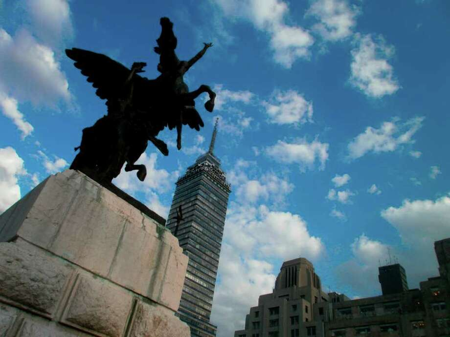 In this photo taken Aug. 19, 2011 and released by blind photographer Jose Sebastian, a sculpture next to Mexico City's Palace of Fine Arts and the Torre Latinoamericana building  stand out against the skyline. Photo: Jose Sebastian, Associated Press / AP