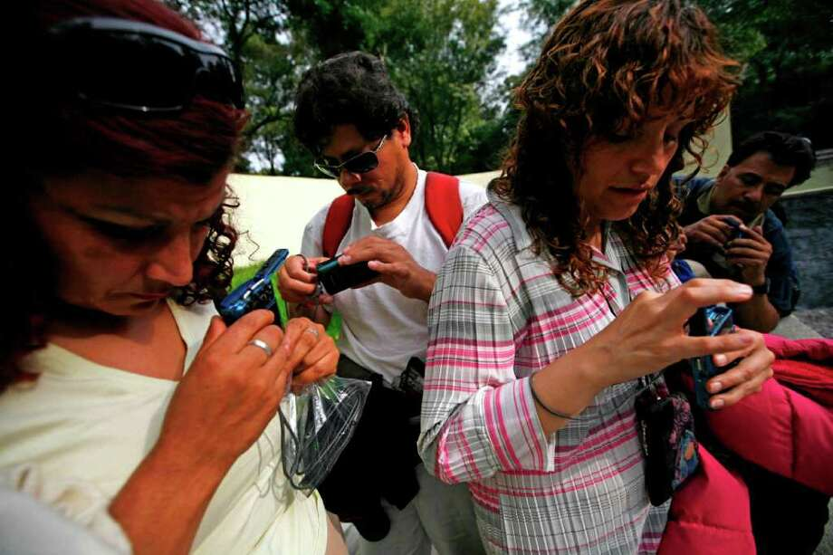 In this photo taken Sept. 7, 2011, blind people feel their cameras during a photography workshop at a park in Mexico City. Photo: Marco Ugarte, Associated Press / AP