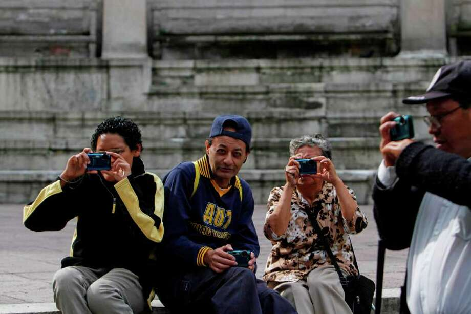 Jesus Garcia, Jose Sebastian Ana Maria Fernandez and Rodrigo Telon, all blind photography students, work during a photo hunting session at a park in Mexico City. The four are part of a group of 30 visually impaired or blind people learning photography. Photo: Marco Ugarte, Associated Press / AP