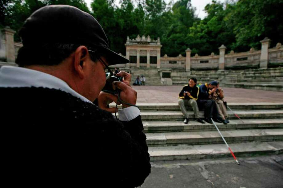 In this photo taken Sept. 7, 2011, Rodrigo Telon Yucute prepares to take a photograph of fellow blind friends at a park in Mexico City. Photo: Marco Ugarte, Associated Press / AP