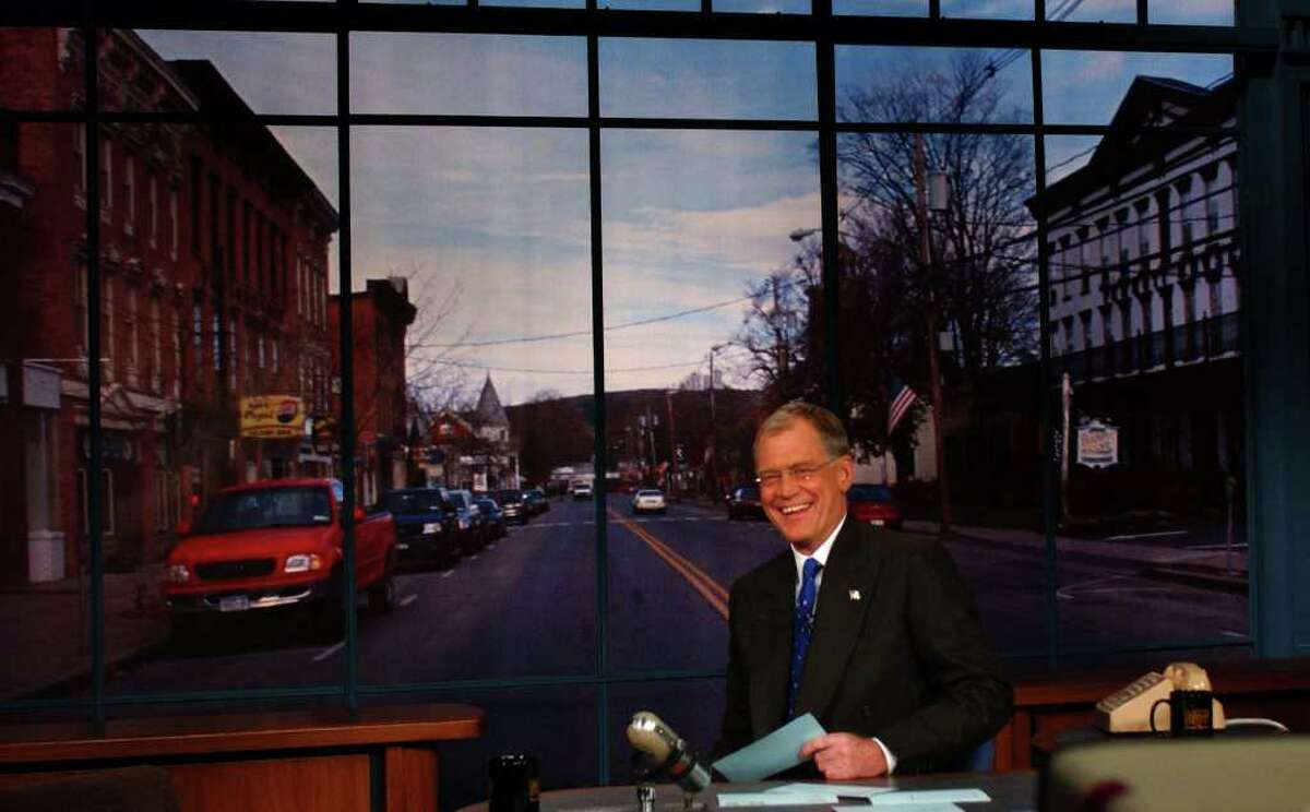 CBS Late Show host David Letterman smiles as the backdrop of Schoharie is lowered in place behind him on Monday, Nov.18, 2002. Letterman bused in 462 residents of Schoharie to be his audience. (CBS Worldwide Inc.)