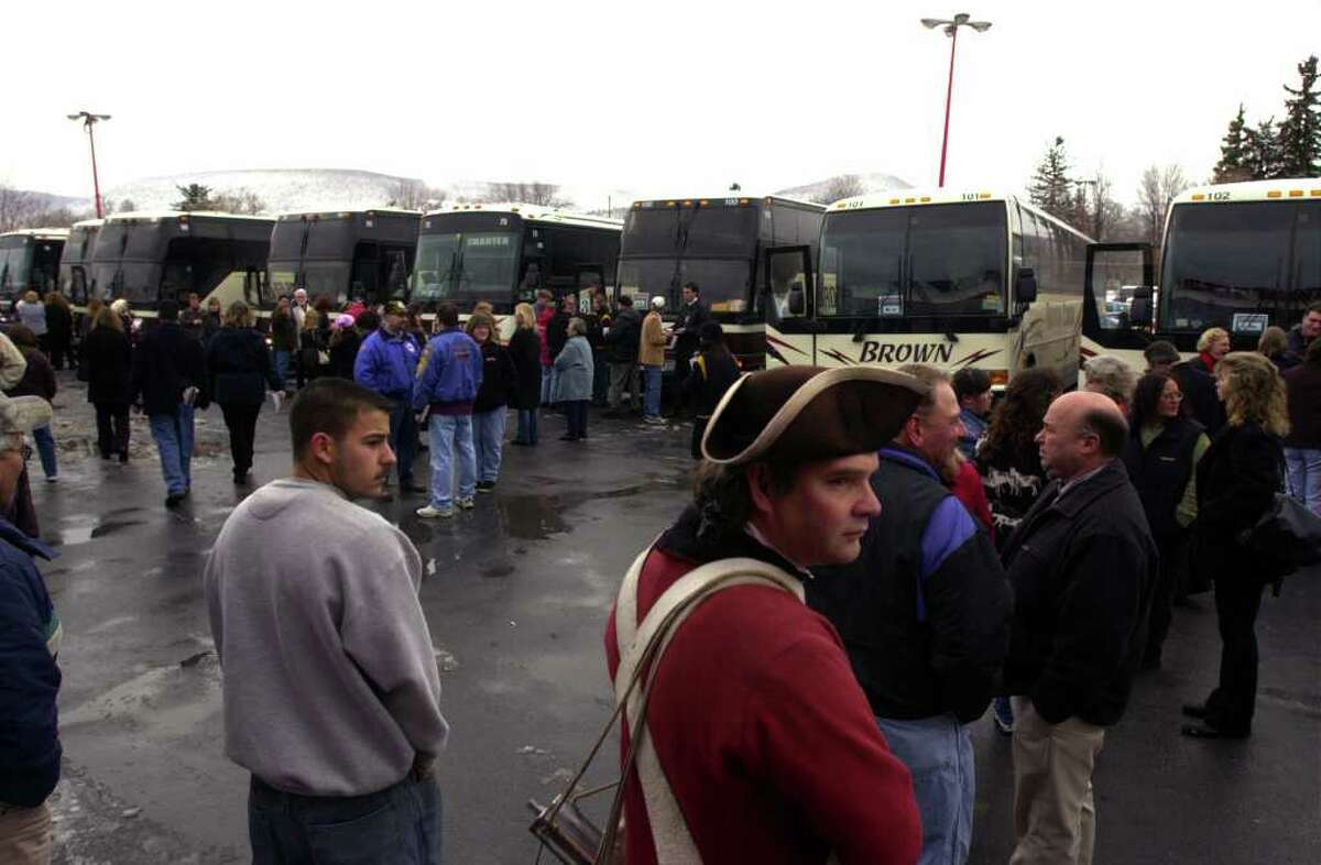 Jeff Tew, foreground right, who works as an interpreter at The Old Stone Fort Museum in Schoharie, seems a bit out of place surrounded by other town residents as they wait to board buses on Monday, Nov. 18, 2002 in Schoharie. Over 450 residents of the town went to New York City to be members in the audience for the taping of a special edition David Letterman show. Letterman has done shows with audiences from major cities, but this was the first time a small community had a special show. The population of the town at the time was 1,033. (Paul Buckowski / Times Union)