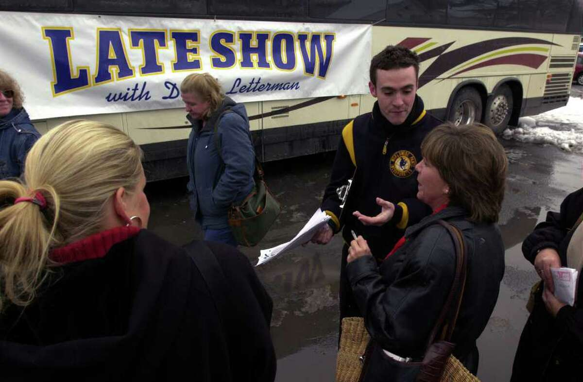 Late Show with David Letterman page, Alex Cuthbertson, second from right, helps Schoharie resident Judy Relyea, right, find her bus on Monday, Nov. 18, 2002, in Schoharie. Over 450 residents of the town took a trip to New York City to be members in the audience for the taping of a special edition David Letterman show. The population of the town at the time was 1,033. (Paul Buckowski / Times Union)