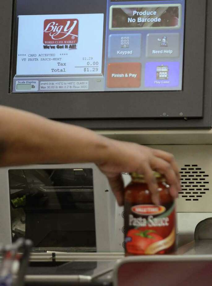 In this Sept. 23, 2011 photo, a customer uses a self-serve checkout station at a Big Y supermarket in Manchester, Conn. A growing number of supermarket chains are bagging their self-serve checkout lanes, saying they can offer better customer service when clerks help shoppers directly. Big Y Foods, which has more than 60 southern New England locations, recently became the latest to announce it's phasing them out. (AP Photo/Jessica Hill) Photo: Jessica Hill / AP2011