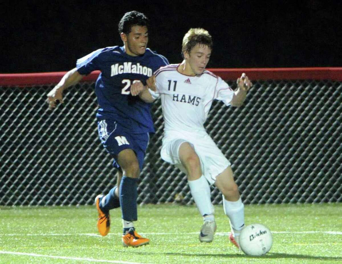 New Canaan's Steven Velente fends off McMahon's Alexis Mayorga as New Canaan High School hosts Brien McMahon in a boys soccer game at New Canaan's Dunning Stadium, Conn., Sept. 26, 2011.