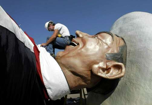 Tim Thibodeaux puts the finishing touches on Big Tex's neck tie before the 52-foot -tall cowboy is lifted up at the State Fair of Texas on Monday, Sept. 26, 2011 in Dallas, Texas. The State Fair of Texas' biggest spokesman was erected ahead of opening day, which will be Friday, Sept. 30, 2011. (AP Photo/The Dallas Morning News, Lara Solt) MANDATORY CREDIT; MAGS OUT; TV OUT; INTERNET USE BY AP MEMBERS ONLY Photo: Lara Solt, Associated Press / The Dallas Morning News
