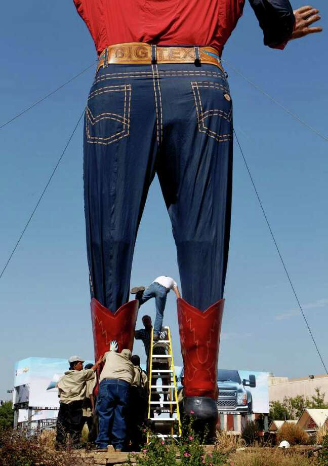 Tim Thibodeaux, top of ladder, climbs out of Big Tex's boot while helping to set up the 52-foot -tall cowboy at the State Fair of Texas on Monday, Sept. 26, 2011 in Dallas. Photo: Lara Solt, Associated Press / The Dallas Morning News