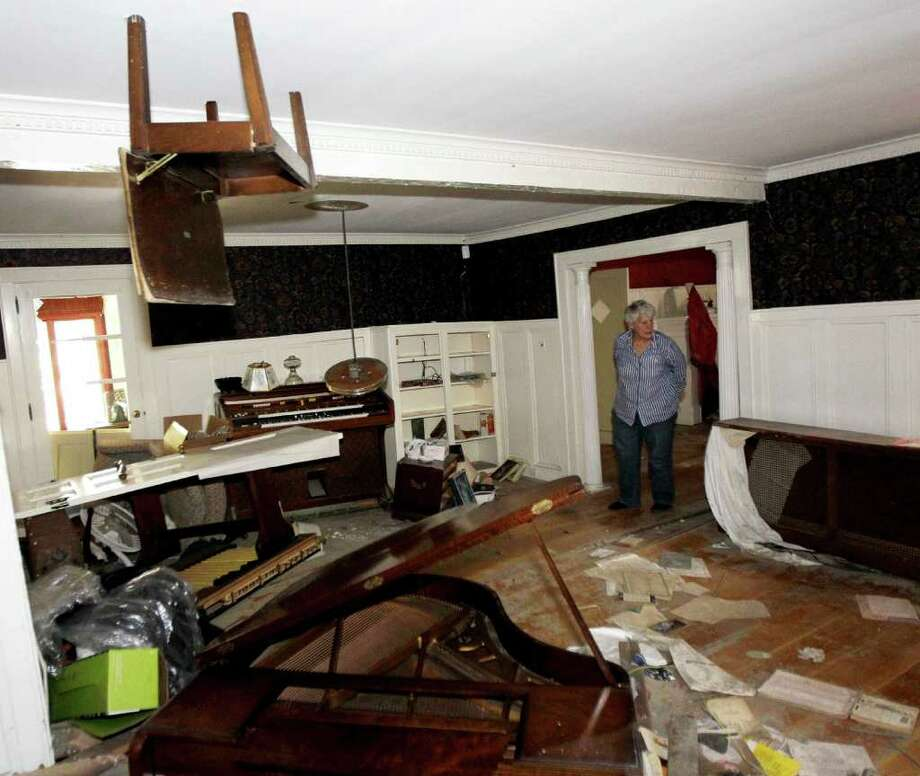 A piano chair hangs from the ceiling in the home of Martha Gordon as she looks through her home destroyed during the flood in the aftermath of Hurricane Irene, Monday, Sept. 26, 2011, in Wayne, N.J. The chair, which was on top of a piano, was lodged into the ceiling when the Ramapo River crested sending floodwaters into the residence. Gordon, who has lived at the house for 50 years, says she has given up and will be tearing the house and moving to Maine. She has talked to FEMA, but doesn't expect any quick relief aid. (AP Photo/Julio Cortez) Photo: Julio Cortez / AP