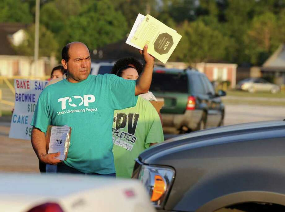 Humberto Garcia hands out pamphlets to parents as they drop their kids off at school, Monday, Sept. 26, 2011, in Pasadena, Texas. Texas cities, counties and school districts may have to return more than $135 million, nearly half of it from public schools, to some of the nation's largest refineries should three commissioners appointed by Gov. Rick Perry grant them a tax refund. (AP Photo/Pat Sullivan) Photo: Pat Sullivan / AP