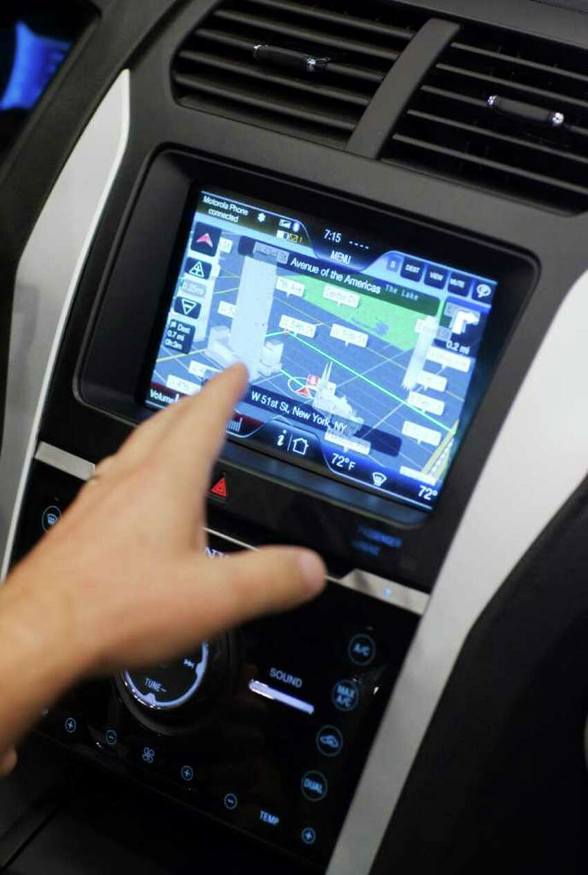 An attendee tries a demonstration of Ford Motor Co.'s SYNC information and entertainment system during the CTIA Enterprise & Applications conference at the Moscone Center in San Francisco, Calif., on Thursday, Oct. 7, 2010. Ford announced the release of a software kit that will allow developers to use existing smartphone applications for voice commands in their Ford vehicles. (David Paul Morris / Bloomberg)