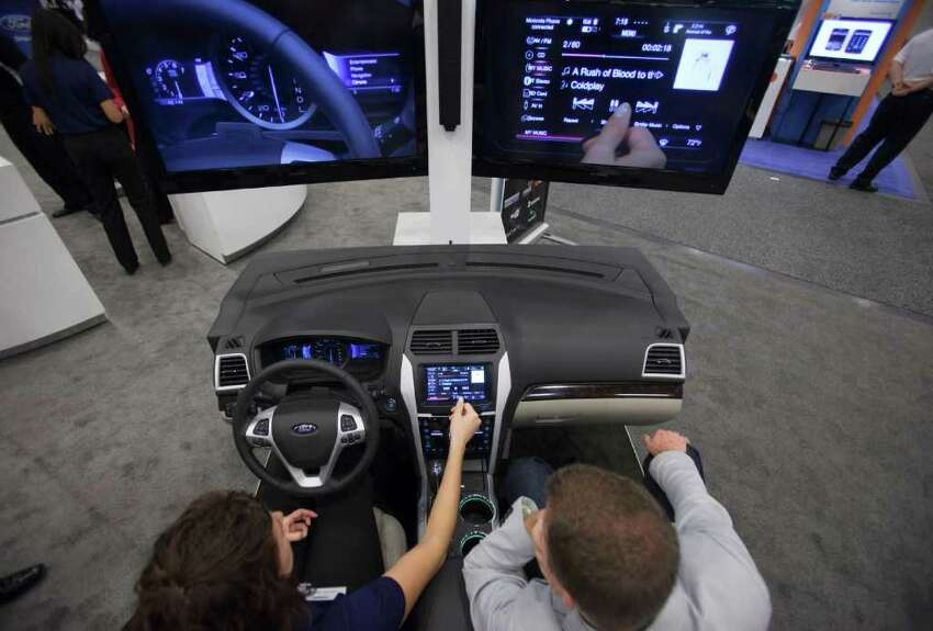 An attendee tries a demonstration of Ford Motor Co.'s Sync information and entertainment system during the CTIA Enterprise & Applications conference at the Moscone Center in San Francisco, California, U.S., on Thursday, Oct. 7, 2010. Ford announced the release of a software kit that will allow developers to use existing smartphone applications for voice commands in their Ford vehicles. Photographer: David Paul Morris/Bloomberg