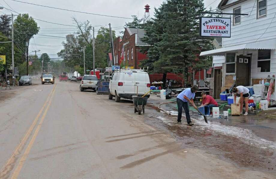 People clean up damaged buildings on Main St. in Prattsville, N.Y. on Sept. 8, 2011. The Schoharie Creek flooded the town after tropical storm Irene.(Lori Van Buren / Times Union) Photo: Lori Van Buren