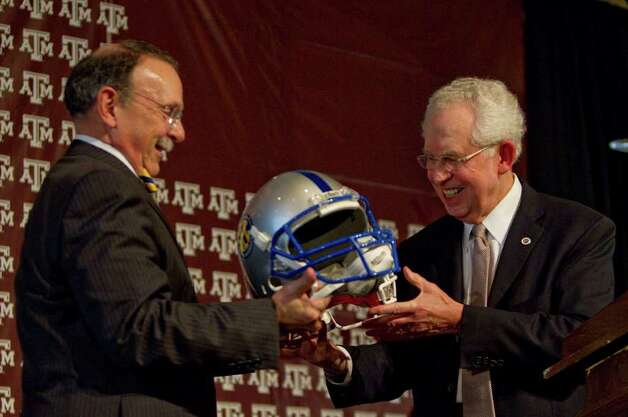 Texas A&M president R. Bowen Loftin, left, and Southeastern Conference commissioner Mike Silve ceremoniously exchange helmets as Texas A&M officially enters the SEC, Monday, Sept. 26, 2011, in Kyle Field in College Station. Photo: Nick De La Torre, Nick De La Torre/Houston Chronicle / © 2011 Houston Chronicle