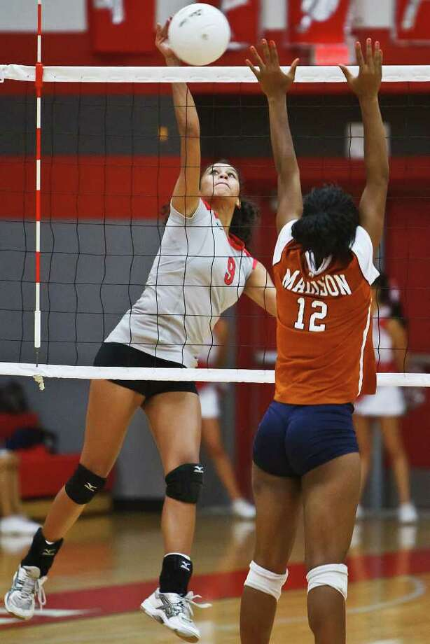 Madison's Tanesha Johnson (right, facing away) had 21 kills and 34 digs as the Mavericks rallied to defeat Reagan in five games in District 26-5A play. It was Madison's first victory against Reagan since October 2003. Photo: Marvin Pfeiffer/mpfeiffer@express-news.net