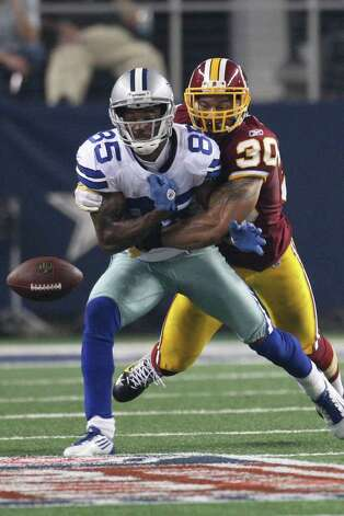 Cowboys wide receiver Kevin Ogletree loses the ball after a hit from Washington Redskins safety LaRon Landry at Cowboys Stadium in Arlington on Monday, Sept. 26, 2011. Photo: JERRY LARA, Jerry Lara/glara@express-news.net / SAN ANTONIO EXPRESS-NEWS