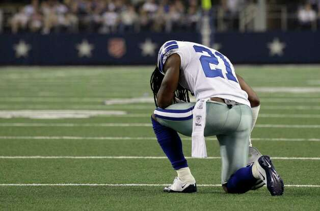Dallas Cowboys cornerback Mike Jenkins kneels before leaving the NFL football game with a left-shoulder injury during the first half against the Washington Redskins on Monday, Sept. 26, 2011, in Arlington. Photo: Tony Gutierrez/Associated Press