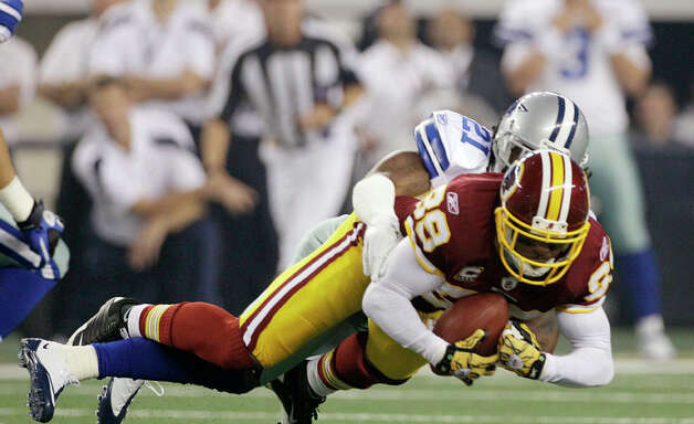 Dallas Cowboys cornerback Mike Jenkins tackles Washington Redskins wide receiver Santana Moss during the first half of an NFL football game Monday, Sept. 26, 2011, in Arlington. Photo: Tony Gutierrez, Tony Gutierrez/Associated Press / AP