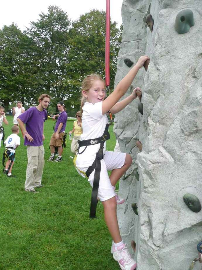 "Molly Braun tries her hand at rock climbing as she makes her way up a practice cliff face at the Greenwich Land Trust's 12th annual Go Wild! fund raising event. ""When I'm up there,"" Braun says, ""it's really exciting."" Photo: Anne W. Semmes"