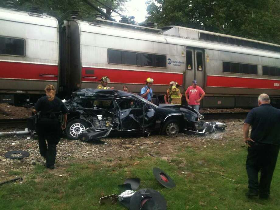 Rescue workers pick through the debris of a car hit by a New Canaan line Metro North train in Springdale, Sept. 27. Photo: Chris Preovolos