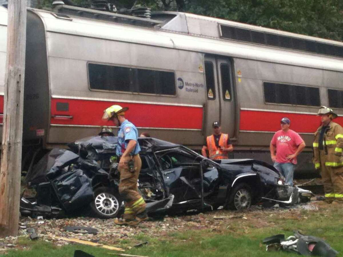 Rescue workers pick through the debris of a car hit by a New Canaan line Metro North train in Springdale, Sept. 27.
