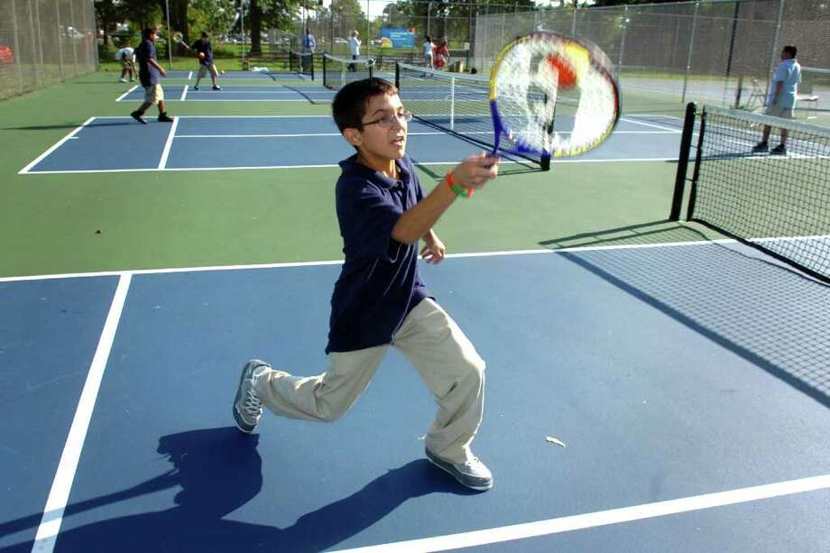 Michael Panheiro, a 7th grader from Blackham School, plays tennis with other students from the Lighthouse Afterschool Program on one of the newly renovated tennis courts in Glenwood Park, in Bridgeport, Conn. Sept. 26th, 2011. Bridgeport has received a $50,000 grant from the United State Tennis Association (USTA) to expand the 10-and-under tennis program and to improve tennis courts throughout the city. Photo: Ned Gerard / Connecticut Post