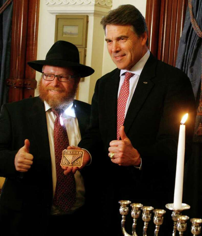 """In this 2010 photo, Texas Gov. Rick Perry, right, and Rabbi Yossi Lazaroff flash the """"Gig 'em, Aggies"""" thumbs-up signal following a symbolic menorah lighting ceremony at the Governor's Mansion. Perry drew some weird looks when he told a New York Times Magazine writer that he was """"more Jewish"""" than people think. Photo: Jack Plunkett, AP / FR59553 AP"""