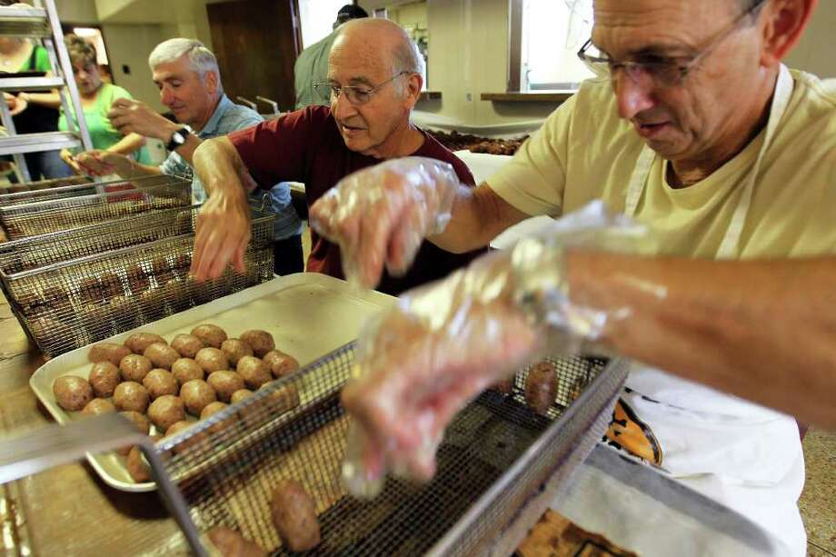 Christopher Columbus Society volunteers, from left, Ralph Paglia, Jim Mezzetti, and Richard Bertani, organize the meatballs into fryer baskets before they are cooked during preparations for the spaghetti dinner at Christopher Columbus Hall, Saturday, September 10, 2011. (Jennifer Whitney/ Special to the San Antonio Express-News) Photo: Jennifer Whitney, Special To The Express-News / special to the Express-News