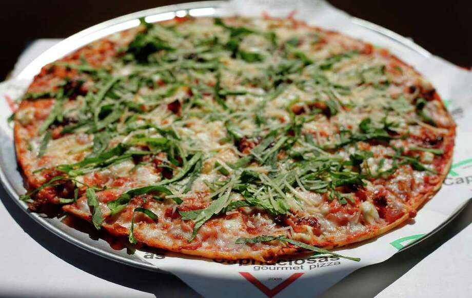 The Delicia pizza is topped with prosciutto, goat cheese, sun-dried tomatoes in olive oil, spinach and parmesan. Photo: KIN MAN HUI, SAN ANTONIO EXPRESS-NEWS / SAN ANTONIO EXPRESS-NEWS