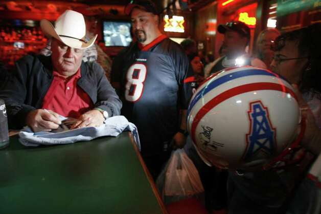 Former Oilers head coach Bum Phillips (cq), left, signs a vintage jacket for Joe Arriaga (cq), (wearing 8) as he and other Ex-Oilers sign autographs during The Luv Ya Blue Reunion for Ex-Houston Oilers and their fans Sunday at Wings 'N More Restaurant and Bar (cq) in The Woodlands (cq). Money made from the reunion benifits the Impact Players Partners, Inc., a foundation to help wounded veterans from the war in Iraq.  (Nick de la Torre/Chronicle) Photo: Nick De La Torre, STAFF / Beaumont