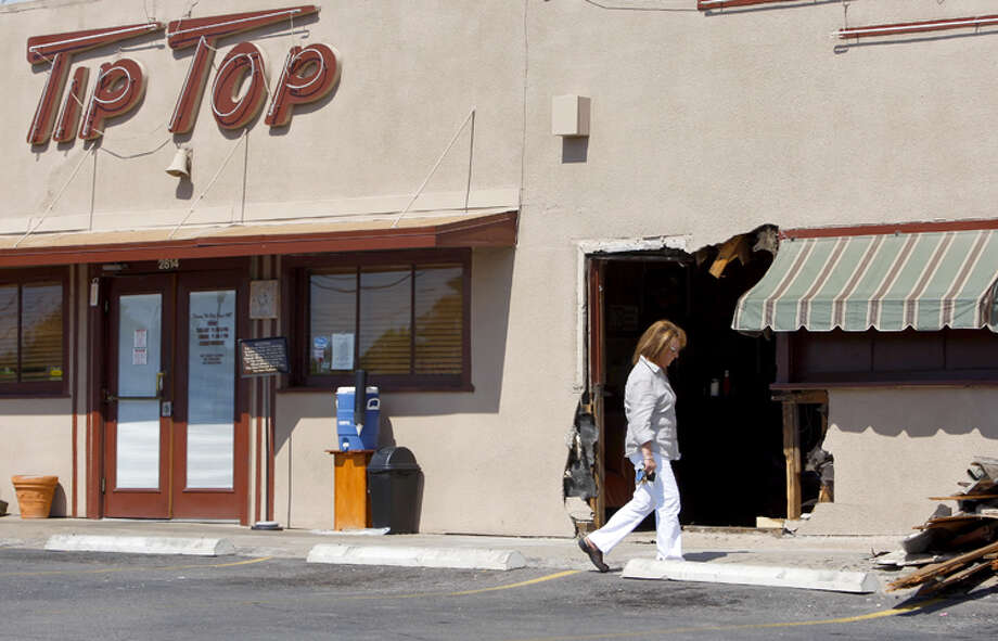 Tip Top Cafe owner Linda DeWese walks Tuesday into the iconic Frederickburg Road restaurant through a hole in the building's front wall after a woman drove her vehicle through it while parking.