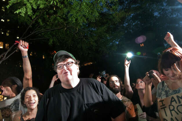 "Members of the crowd react during a visit by filmmaker Michael Moore to the ""Occupy Wall Street"" protest in Zuccotti Park in New York, Monday, Sept. 26, 2011. The protesters, many of whom are camping out in the lower Manhattan plaza to speak out against corporate greed and social inequality, got a morale boost from Moore, who told the crowd they were the start of something big. (AP Photo/Stephanie Keith) Photo: Stephanie Keith"