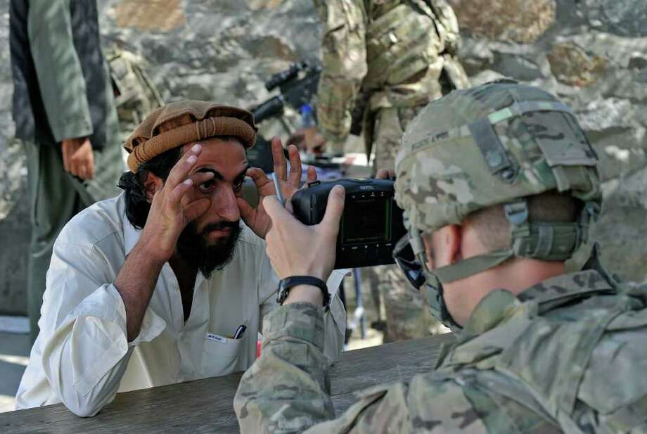 TAUSEEF MUSTAFA: AFP/GETTY IMAGES SECURITY: Spc. Charleston Robert on Tuesday scans eyes of an Afghan man with an automatedbbiometric identification system during a mission near the Pakistan border. Photo: TAUSEEF MUSTAFA / AFP