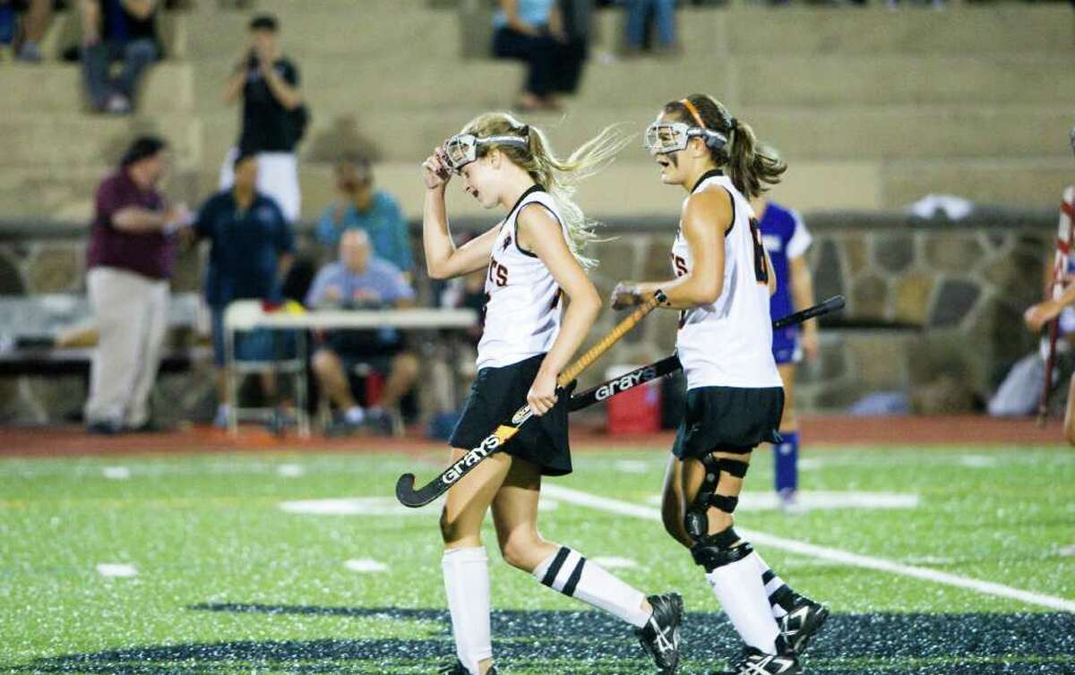 Stamford's Maddy Burns, left, and teammate Kelsey Cognetta head back to center field after Burns' goal as Stamford High School hosts Westhill in a field hockey game in Stamford, Conn., Sept. 27, 2011.