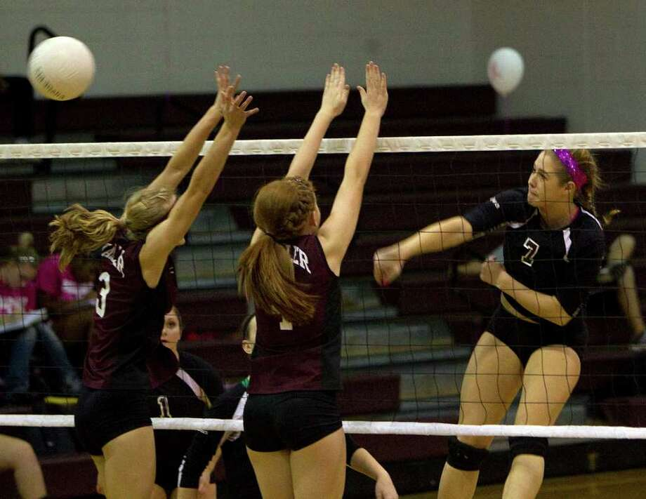 Magnolia's Madison Butler (7) spikes the ball past Waller's Taylor Thomas (3) and Sara DeBerry (4). Photo: Johnny Hanson, Houston Chronicle / © 2011 Houston Chronicle