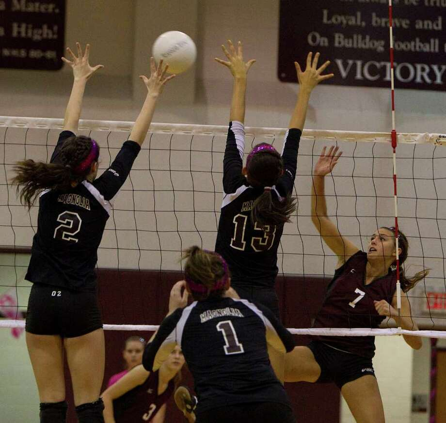 Waller's Morgan Heise (7) spikes the ball into Magnolia's Chelsea Reynolds (2) and Morgan Miller (13). Photo: Johnny Hanson, Houston Chronicle / © 2011 Houston Chronicle