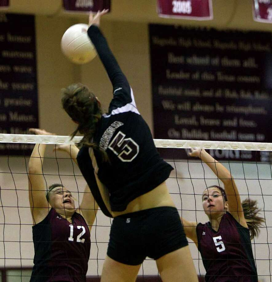 Waller's Kelsey Johnson (12) and McKenzie Bryant (5) prepare for the spike from Magnolia's Kylie Randall. 