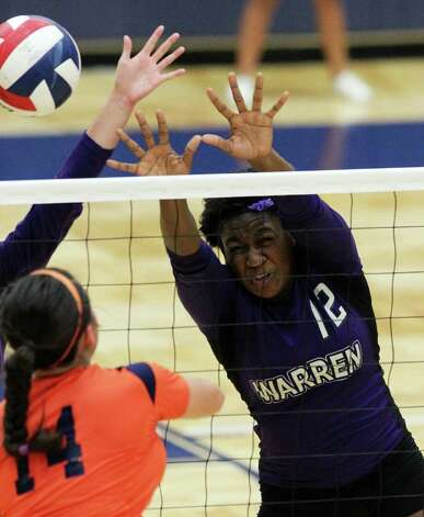 Warren's Laycia Robinson (12) assists with a block attempt against Brandeis' Analise Cardenas (14) during their match at Paul Taylor Fieldhouse on Tuesday, Sept. 27, 2011. Kin Man Hui/kmhui@express-news.net Photo: Kin Man Hui, -- / San Antonio Express-News