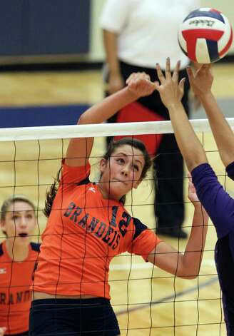 Brandeis' Cassidy Acord (12) hits through a Warren blocker during their match at Paul Taylor Fieldhouse on Tuesday, Sept. 27, 2011. Kin Man Hui/kmhui@express-news.net Photo: Kin Man Hui, -- / San Antonio Express-News