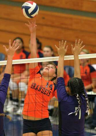 Brandeis' Analise Cardenas (14) stretches to clear a shot against Warren's Ariana Gallardo (07) during their match at Paul Taylor Fieldhouse on Tuesday, Sept. 27, 2011. Kin Man Hui/kmhui@express-news.net Photo: Kin Man Hui, -- / San Antonio Express-News
