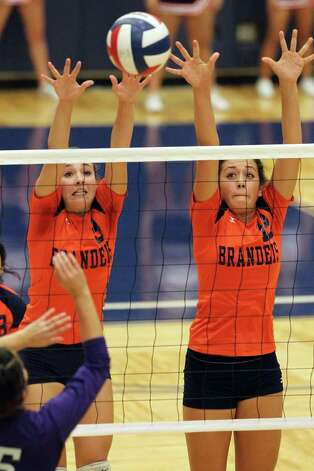 Brandeis' Katie MacLeay (09) and Cassidy Acord (12) stretch for an attempted block against Warren during their match at Paul Taylor Fieldhouse on Tuesday, Sept. 27, 2011. Kin Man Hui/kmhui@express-news.net Photo: Kin Man Hui, -- / San Antonio Express-News